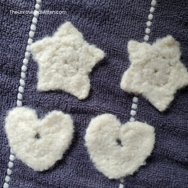 Felted Crochet hearts and stars drying on a towel.