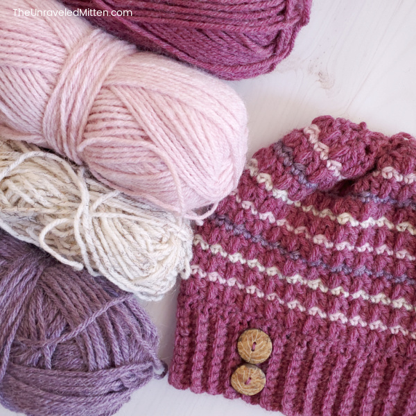 Striped crochet hat with button next to yarn.