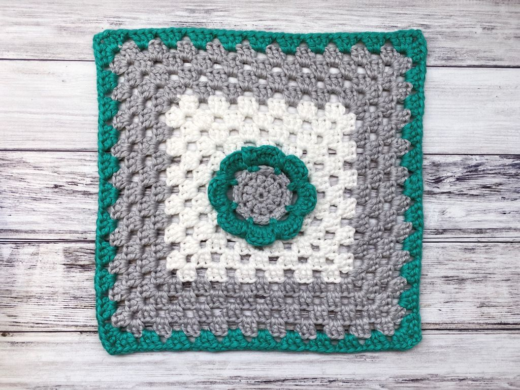 Teal, gray and white granny square with a floral center designed by Love Life Yarn for the 2021 Stash Busting Crochet Along on The Unraveled Mitten