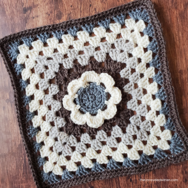 Grey, brown, light grey and cream granny square with a floral center. Desgined by Love Life Yarn for 2021 Stash Busting Crochet Along on The Unraveled Mitten
