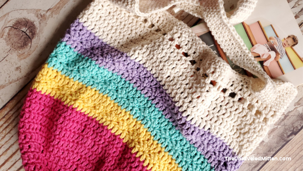 Crochet market bag with bright rainbow colors and neutral top and straps. Book shown halfway into crochet bag, yarn and hook also pictured.